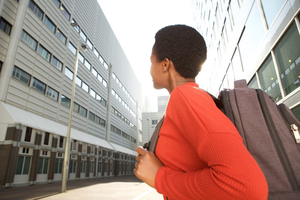 behind of african female student with bag in city